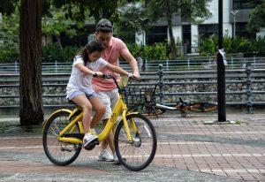 padre aiuta la figlia ad andare in bici