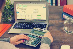 donna con pc e calcolatrice in mano